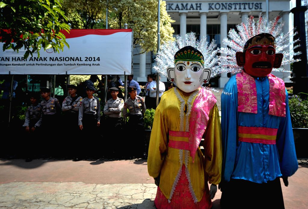 Two Ondel-Ondel giant puppets stand in front of Indonesian police officers while they are deployed to secure the Constitutional Court in Jakarta, Indonesia, Aug. 5, .