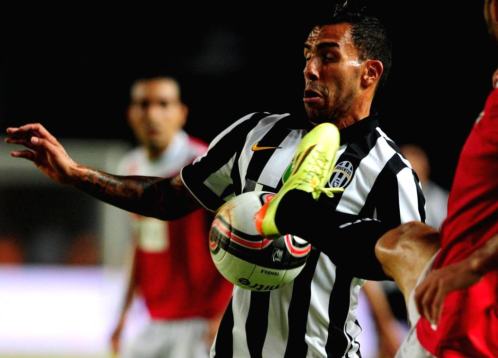Juventus's Carlos Tevez vies with Indonesia ISL All-Stars players during a friendly football match at Bung Karno stadium in Jakarta, Indonesia, Aug. 6, 2014. ...
