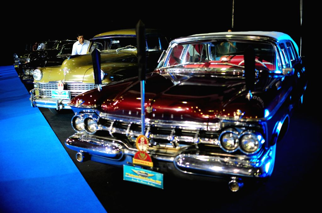 A visitor looks at a classic car at the 7th Indonesia Classic Car Show 2013 in Jakarta, Indonesia, Dec. 20, 2013. The biggest and largest International classic
