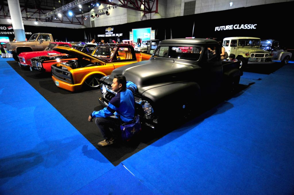 A visitor poses in front of a classic car at the 7th Indonesia Classic Car Show 2013 in Jakarta, Indonesia, Dec. 20, 2013. The biggest and largest ...