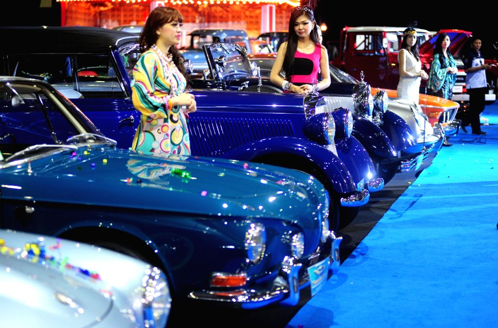 Models stand beside classic cars at the 7th Indonesia Classic Car Show 2013 in Jakarta, Indonesia, Dec. 20, 2013. The biggest and largest International classic