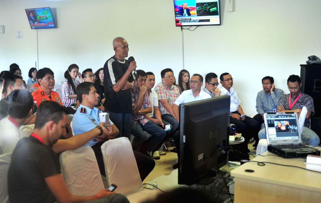 Family members of people on missing AirAsia flight QZ8501 attend a tele-conference with member of search and rescue team at Juanda International Airport in ...