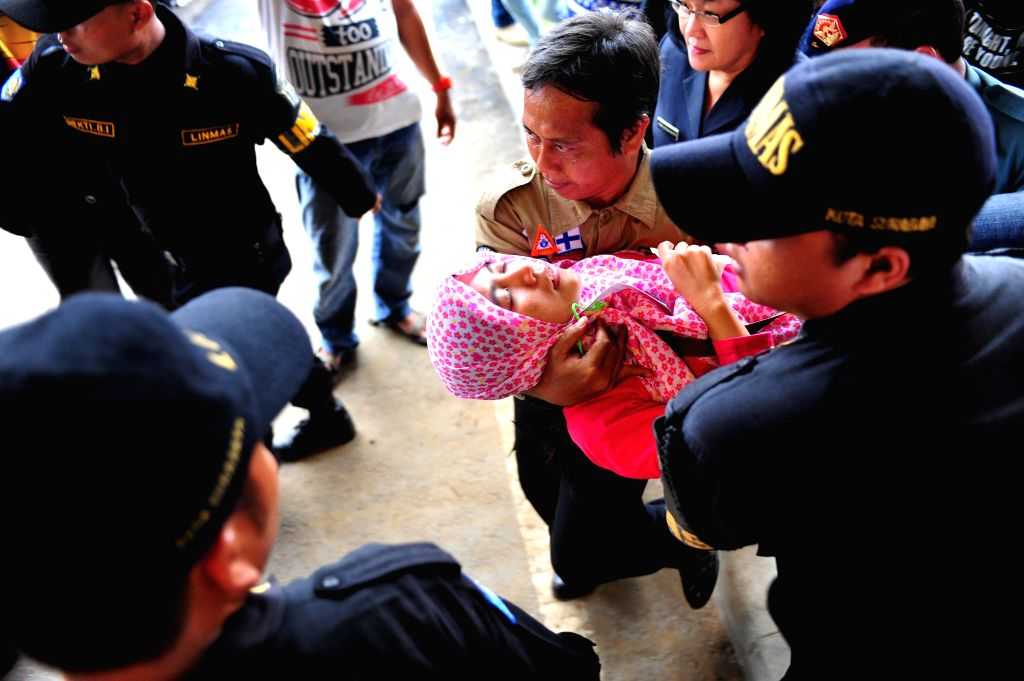Medical staffs carry away a woman at Juanda International Airport in Surabaya, Indonesia, Dec. 30, 2014. Rescuers on Tuesday saw a shadow believed to be part of a ..