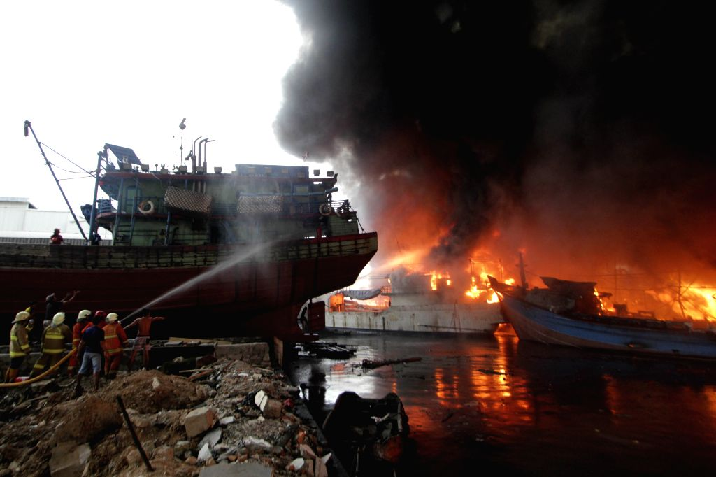 JAKARTA, Feb. 23, 2019 - Firefighters try to extinguish the burning fishing boats at Muara Baru Port in Jakarta, Indonesia. Feb. 23, 2019.