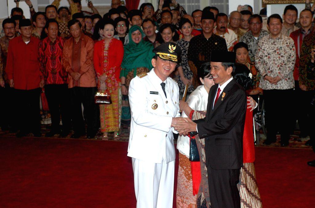 "Jakarta (Indonesia): Indonesian President Joko Widodo (R) shakes hands with new Jakarta governor Basuki Tjahaja Purnama better known by his nickname ""Ahok"" after he sworn at President ..."