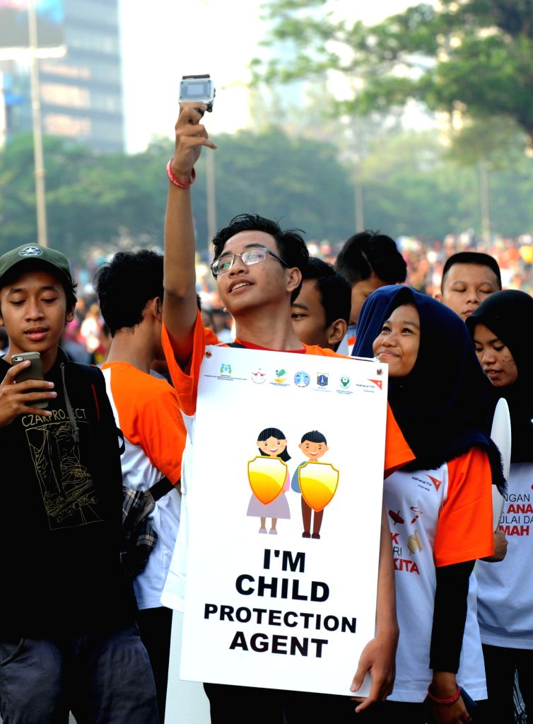 JAKARTA, Jul 24, 2016 - A man holding a banner attend a campaign for child protection and anti-violence against children during the commemoration of National Children's Day in Jakarta, Indonesia, ...