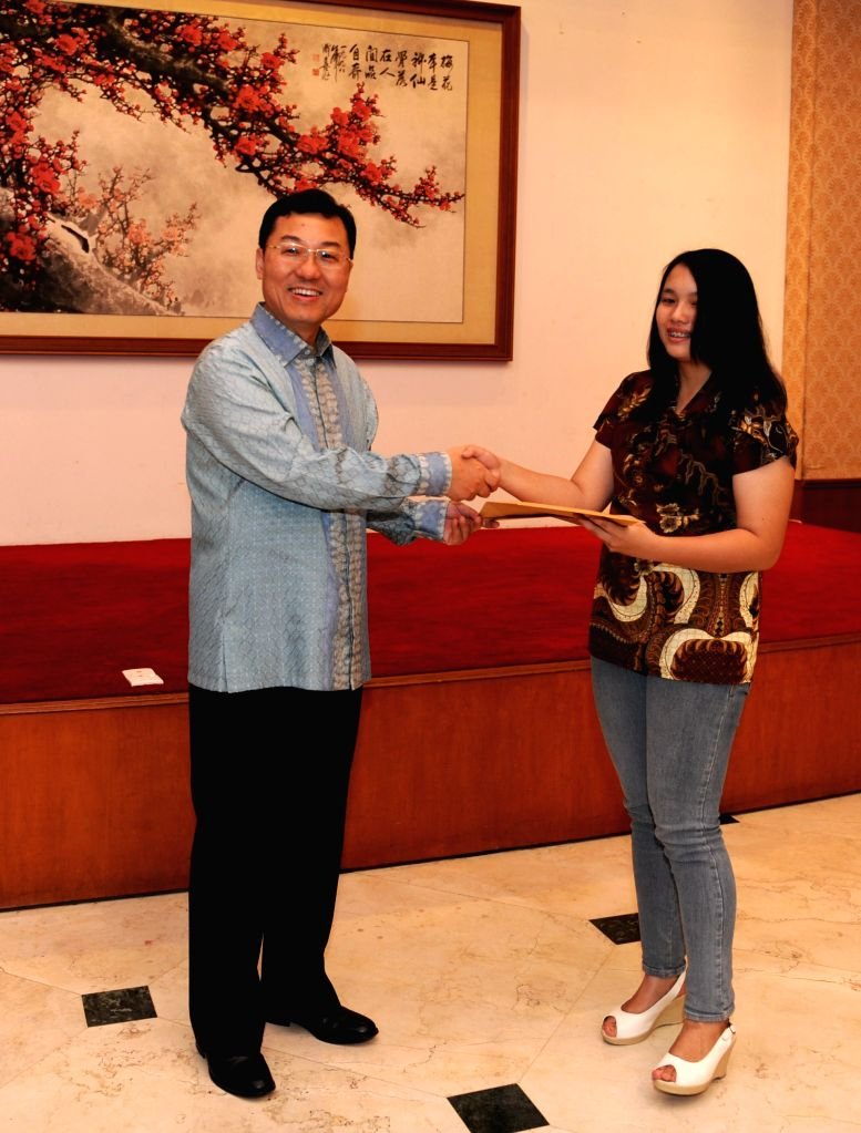 Chinese ambassador to Indonesia Xie Feng (L) awards an Indonesian student with the Chinese government scholarship in 2014-2015 academic year, in Jakarta, Indonesia,