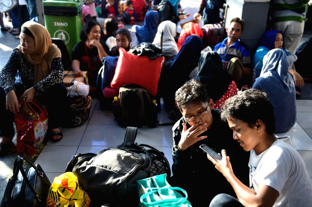 JAKARTA, July 4, 2016 - People wait for trains at a train station in Jakarta, Indonesia, July 4, 2016. Muslims across Indonesia will celebrate the Eid al-Fitr festival, which marks the end of the ...