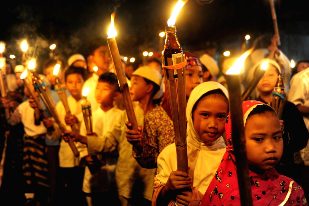 Indonesian Muslim children hold bamboo torches during a parade celebrating the upcoming holy fasting month of Ramadan in Jakarta, Indonesia, June 27, 2014. ...