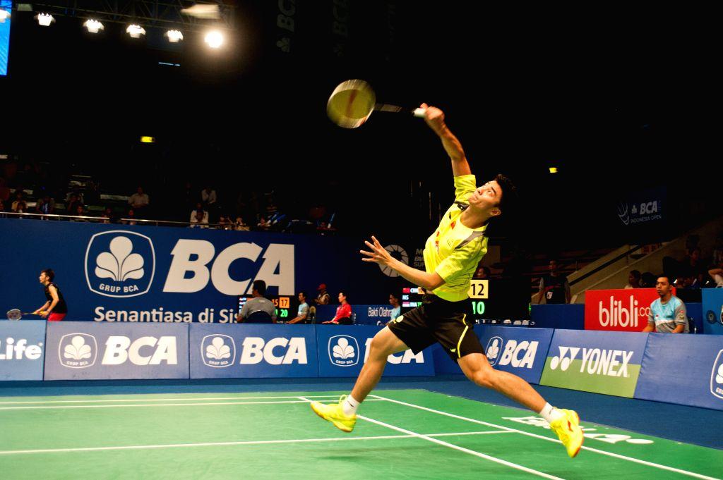 Chen Yuekun of China returns the shuttlecock to Andre Kurniawan Tedjono of Indonesia during the qualification round 2 at BCA Indonesia Open 2014 at Istora Senayan ..