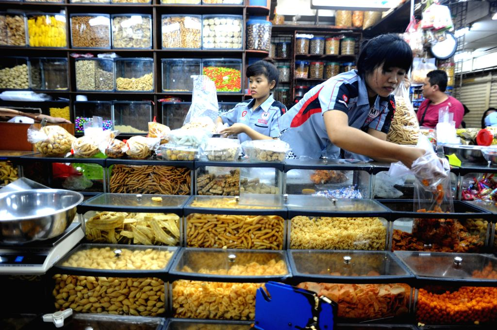 JAKARTA, June 23, 2016 - Staff workers help customers select traditional cookies and snacks for the upcoming Eid al-Fitr festival at Jatinegara market in Jakarta, Indonesia, June 23, 2016. Muslims ...
