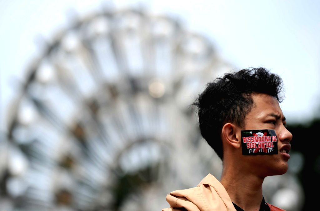 An Indonesian Muslim student with an anti-ISIS (the Islamic State in Iraq and Syria) sticker on his face attends an anti-ISIS rally in Jakarta, Indonesia, March ...