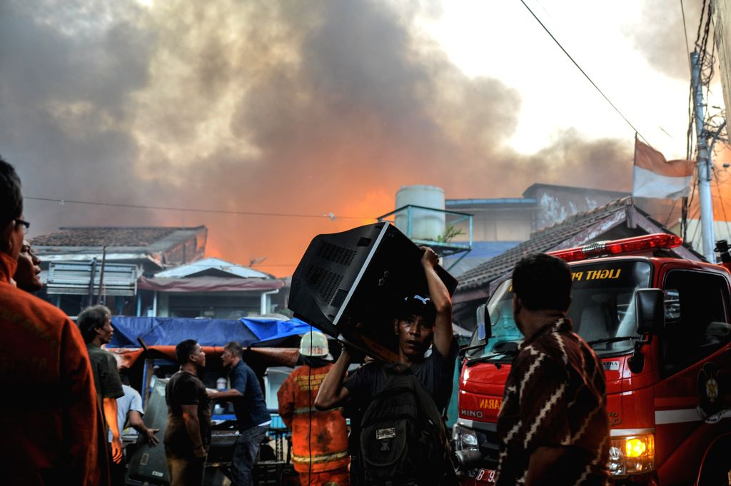 A resident salvages a television from his house during a fire at Tanah Abang in Jakarta, Indonesia, March 5, 2015. As many as 23 fire engines were deployed to ...