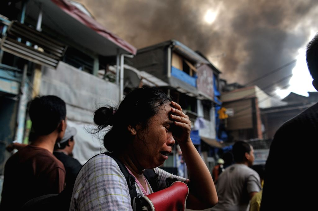 A woman cries after knowing her house caught fire at Tanah Abang in Jakarta, Indonesia, March 5, 2015. As many as 23 fire engines were deployed to extinguish the ...