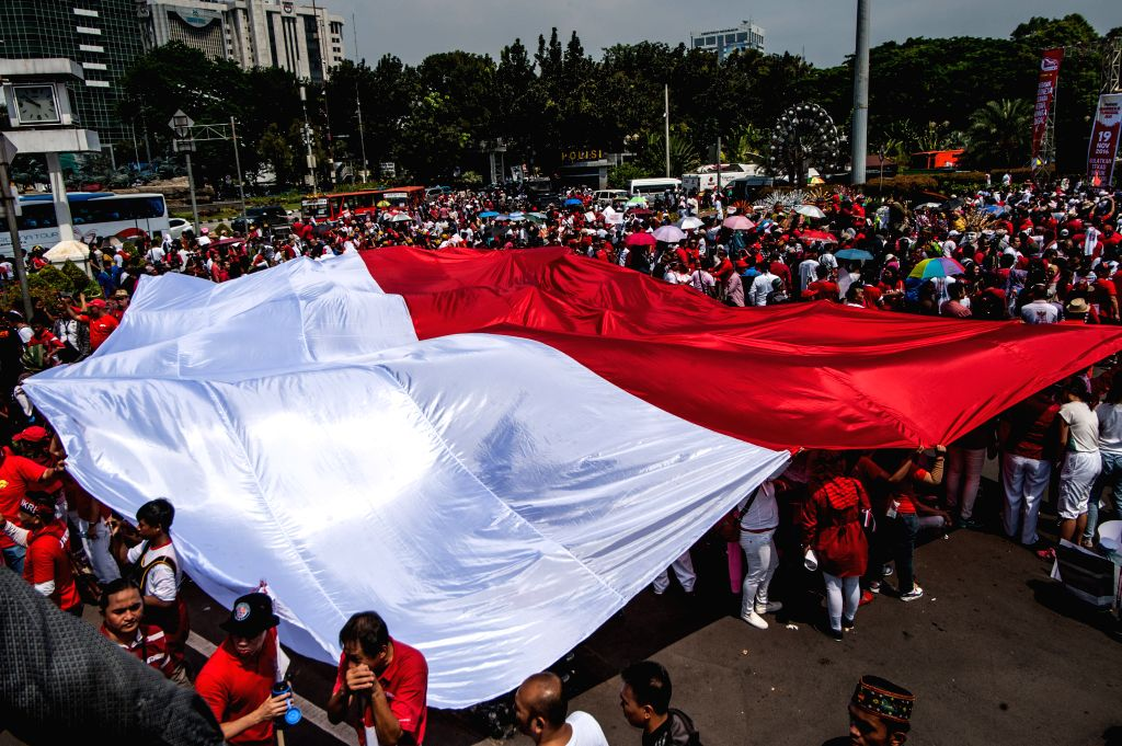 JAKARTA, Nov. 19, 2016 - People walk under a giant Indonesian national flag during the Bhinneka Tunggal Ika (Unity in Diversity) Parade in Jakarta, Indonesia, Nov. 19, 2016. Hundreds of people staged ...