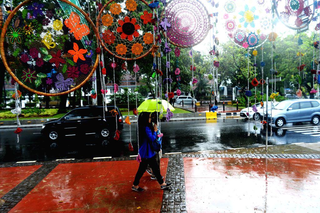 JAKARTA, Sept. 19, 2016 - People holding umbrellas walk in the rain in Jakarta, Indonesia, Sept. 19, 2016.