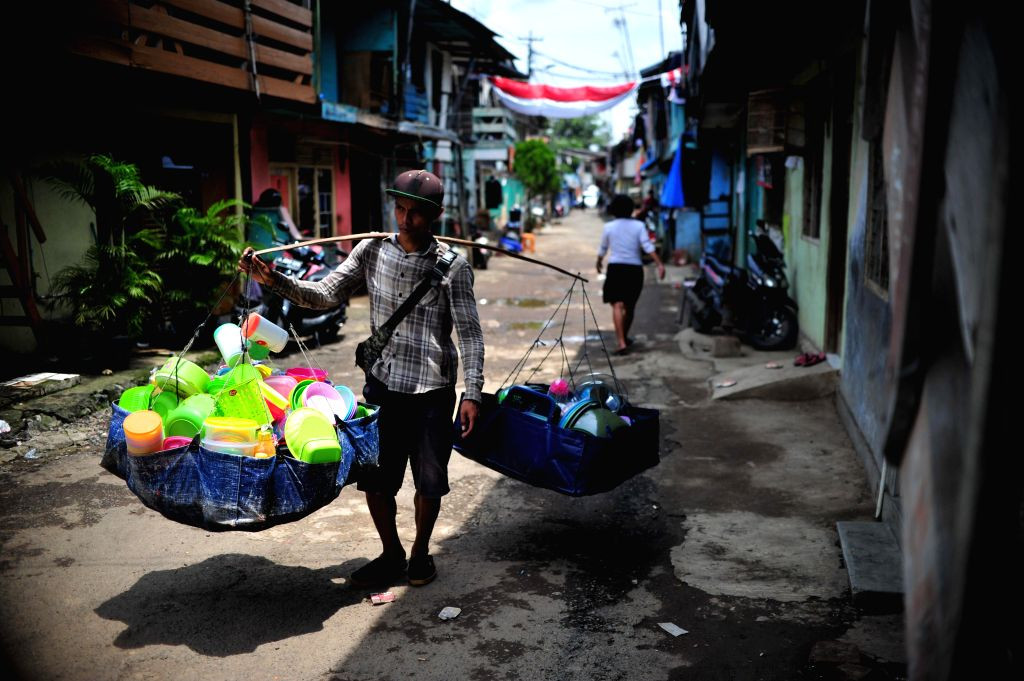 JAKARTA, Sept. 20, 2016 - A vendor carrying goods walks in an area which will be demolished by authorities near the Ciliwung River in Jakarta, Indonesia, Sept. 20, 2016. Demolition is performed for ...