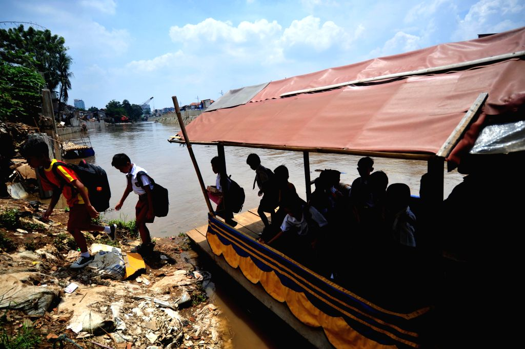 JAKARTA, Sept. 20, 2016 - School children get off a wooden boat on the bank of the Ciliwung River in Jakarta, Indonesia, Sept. 20, 2016. Demolition is performed for widening the Ciliwung River in ...