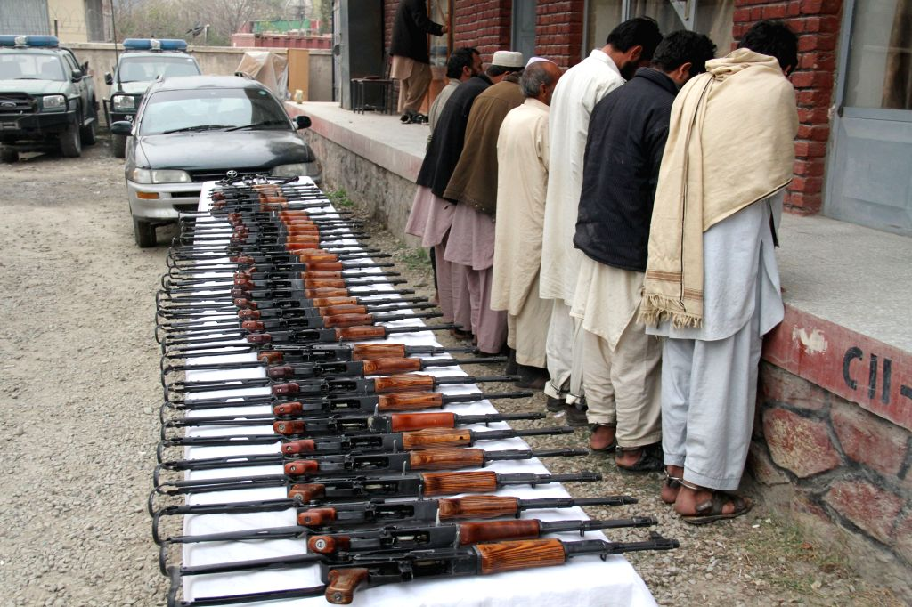 Suspected militants arrested by Afghan police stand as their weapons are presented to the media at Jalalabad, capital city of eastern Nangarhar province, Jan. 12,