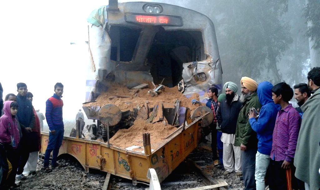 People stand near an accident area of a train which hit a tractor at a railway crossing in Jalandhar on Jan 3, 2015.