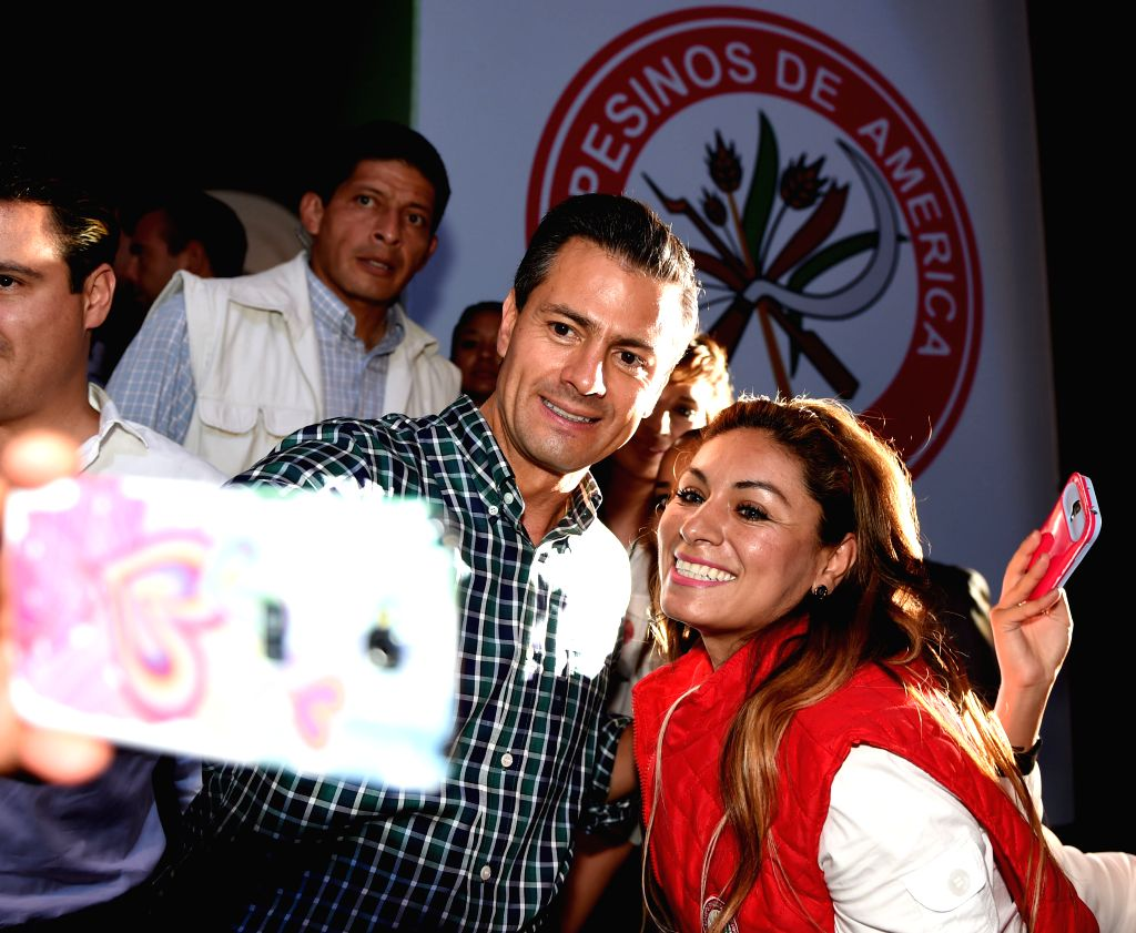 Image provided by Mexico's Presidency, shows Mexican President, Enrique Pena Nieto (L), posing for a picture with a supporter, during the closing ceremony of the ...