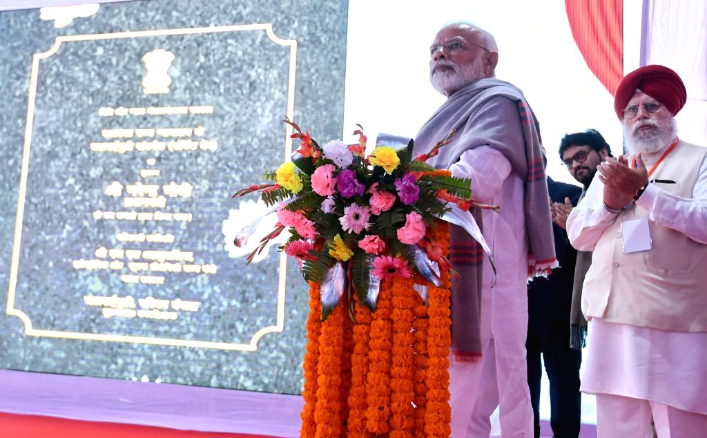 Jalpaiguri: Prime Minister Narendra Modi inaugurates the four laning of the Falakata - Salsalabari section of NH-31 D and Circuit Bench of Calcutta High Court in Jalpaiguri, West Bengal on Feb 8, 2019. Also seen Union MoS Electronics and Information  - Narendra Modi