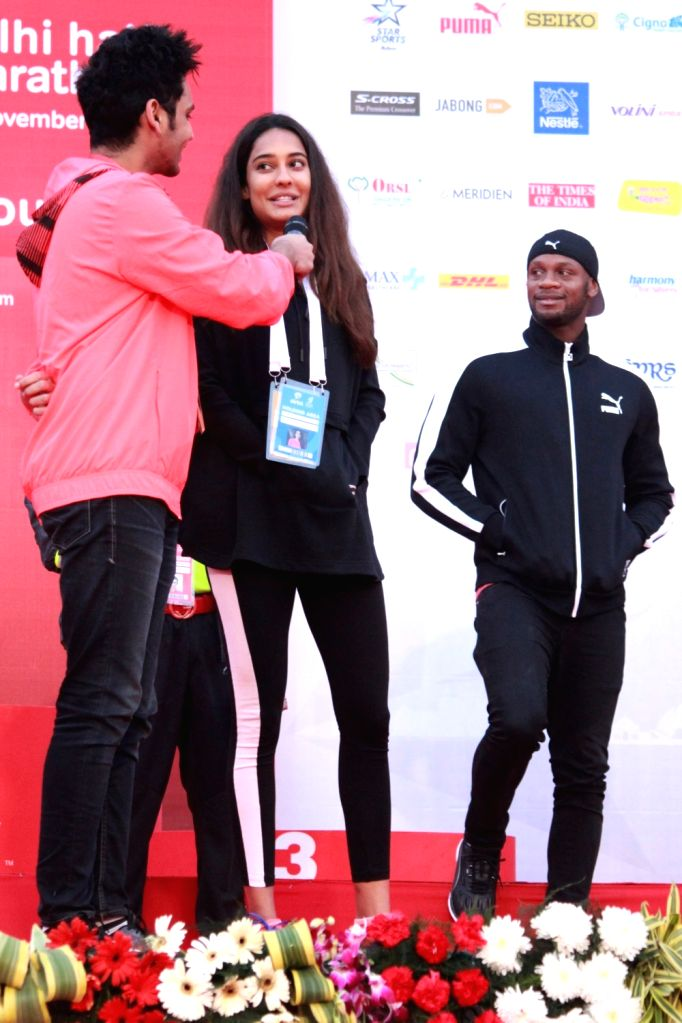 Jamaican sprinter Asafa Powell (R) during the Airtel Delhi Half Marathon 2016 at Jawaharlal Nehru Stadium in New Delhi, on Nov 20, 2016.