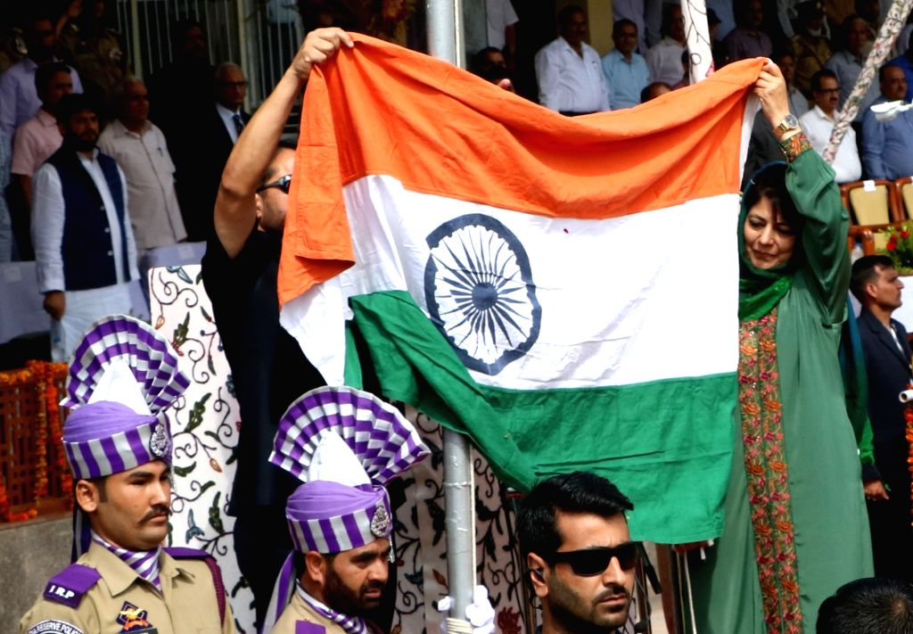 Jammu and Kashmir Chief Minister Mehbooba Mufti holds the national flag during an Independence Day programme at Bakshi stadium in Srinagar on Aug 15, 2016. - Mehbooba Mufti