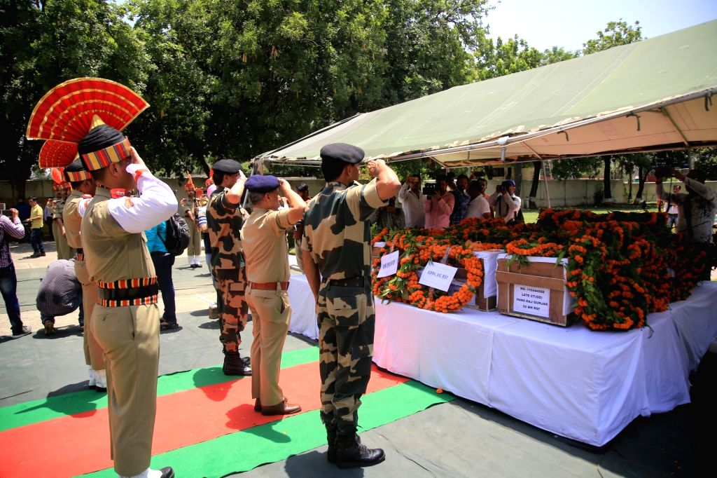 :Jammu: BSF soldiers pay tribute to their colleagues killed in an unprovoked Pakistan ceasefire violation on the international border in Jammu and Kashmir; in Jammu on June 13, 2018. Four BSF ...