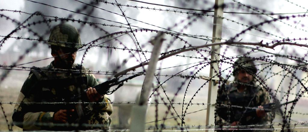 Soldiers stand guard at the Indo-Pak border fence at Jogwana Post of Jammu's R S Pura Sector in wake of US President Barack Obama's visit to India in New Delhi, on Jan 25, 2015.
