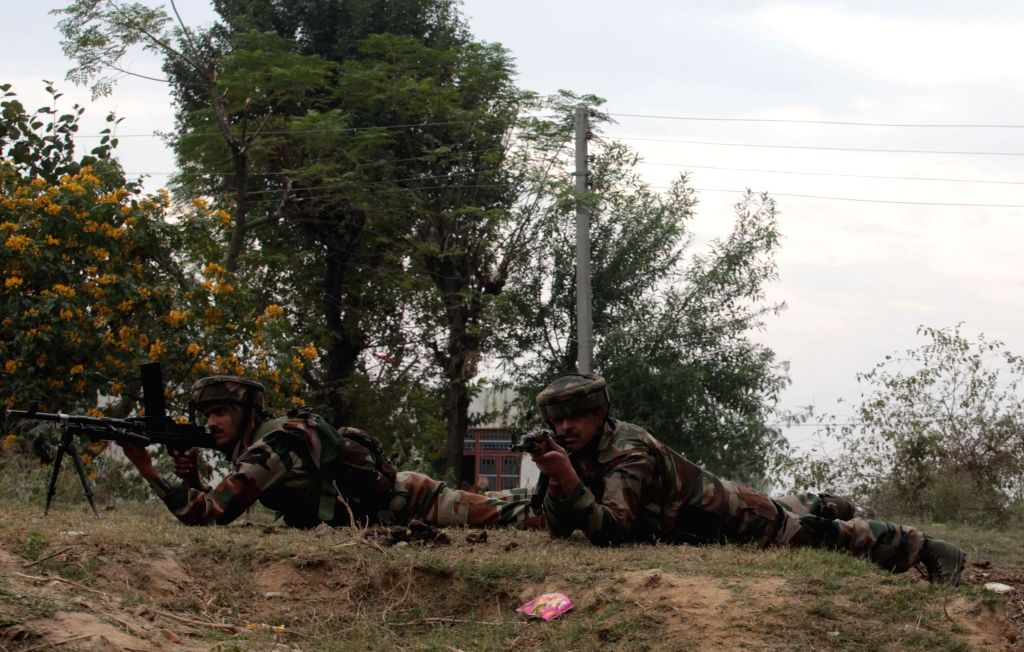 Soldiers take position during a gun battle between the security forces and militants near the international border in Jammu district's Arnia area on Nov 27, 2014.