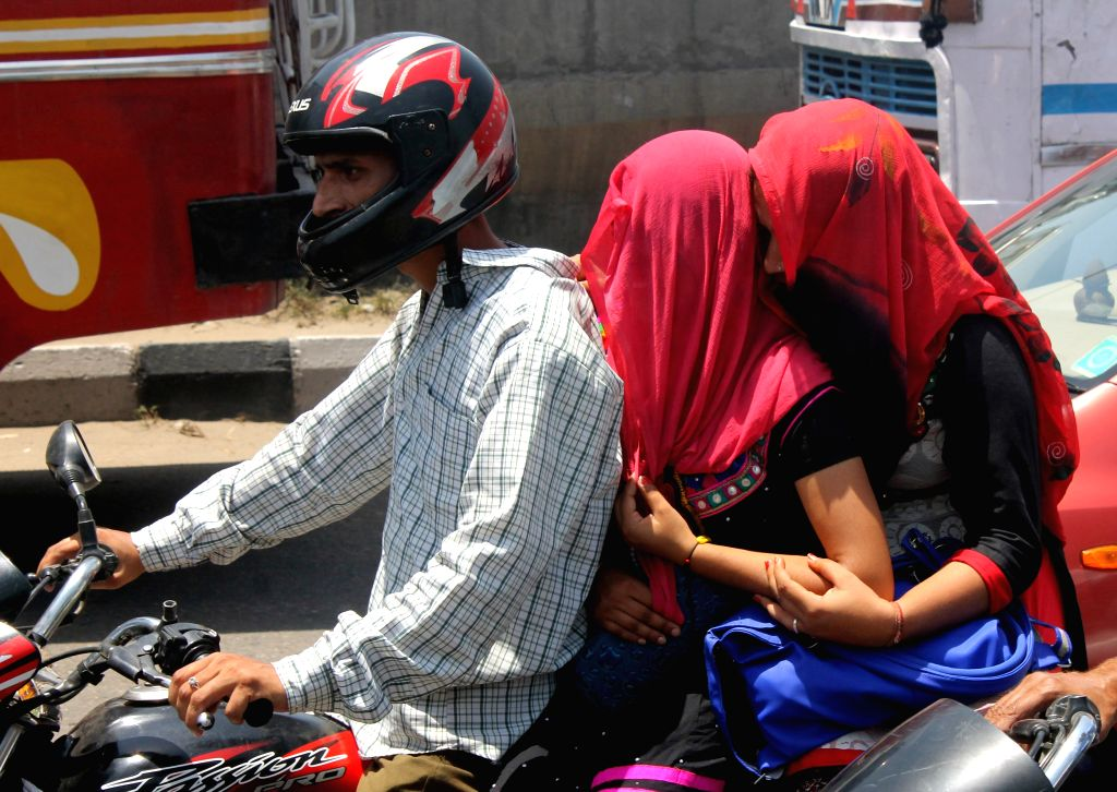 Jammu: Women cover their heads so as to avoid direct sun contact in Jammu. (Photo: IANS)