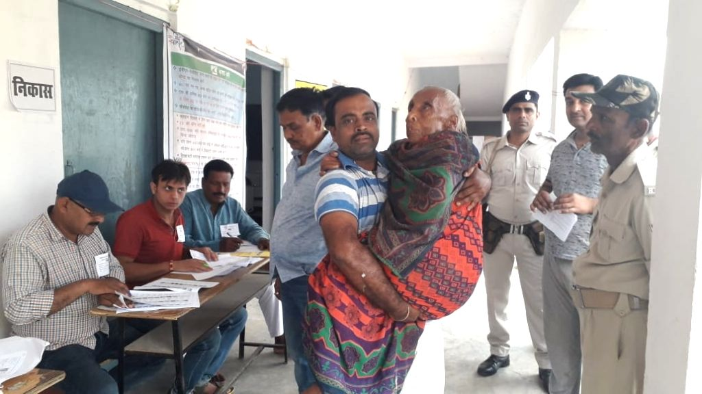 Jamui: An old woman being carried to a polling station to cast vote for Lok Sabha election, in Bihar's Jamui, on April 11, 2019. (Photo: IANS)