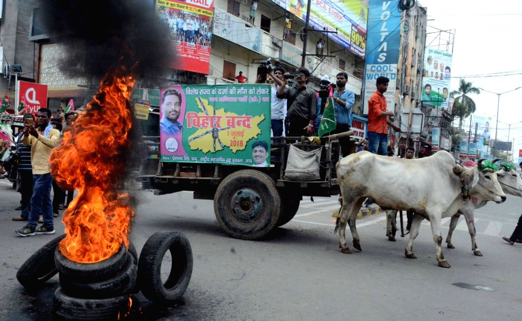 Jan Adhikar Party (JAP) workers burn tires as they stage a demonstration during Bihar bandh called by their party to press for their various demands, in Patna on July 7, 2018.