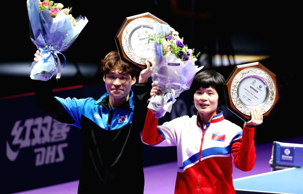 Jang Woo-jin of South Korea (L) and Cha Hyo-sim of North Korea pose for a photo after capturing the gold medal in the mixed doubles at the International Table Tennis Federation (ITTF) World ...
