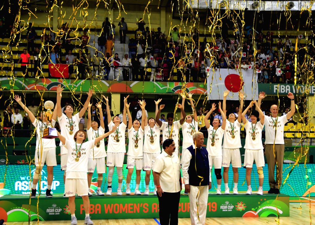 Japanese players celebrate after winning the 2019 FIBA Women's Asia Cup trophy by defeating China at Sree Kanteerava Stadium, in Bengaluru on Sep 29, 2019. Also seen Karnataka Governor ...