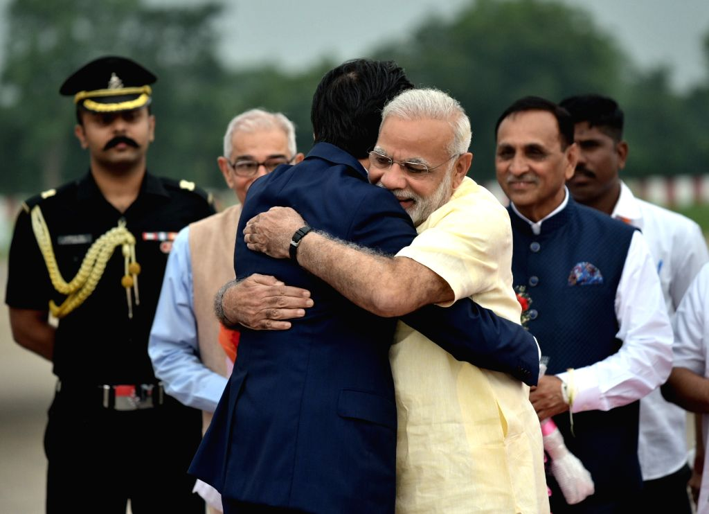 Japanese Prime Minister Shinzo Abe being welcomed by Prime Minister Narendra Modi at Ahmedabad airport, Gujarat on Sept 13, 2017. Also seen Gujarat Governor O.P. Kohli and Chief Minister ... - Shinzo Abe, Narendra Modi and P. Kohli