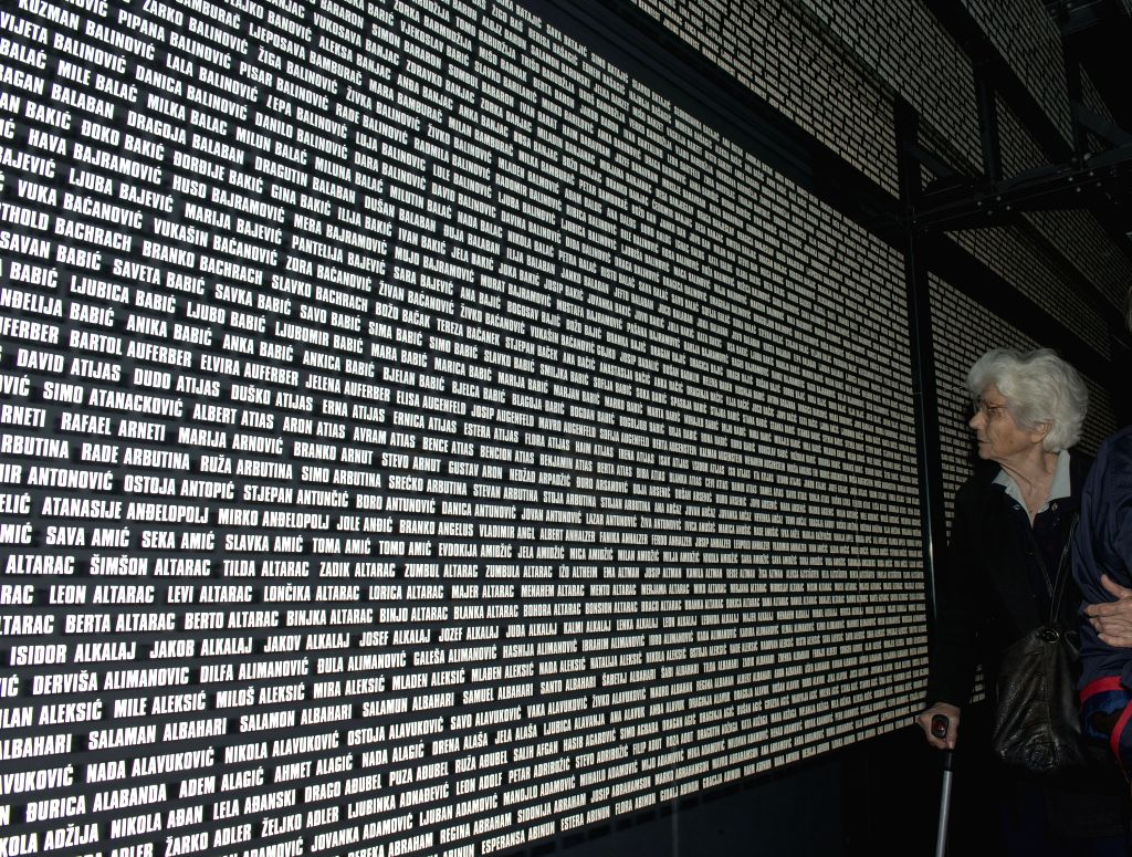A woman searchs for the name of her relative killed in former Nazi concentration camp during the official commemoration in Jasenovac, Croatia, April 22, 2012. ...
