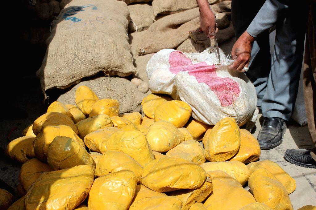 Afghan policemen display drugs in Jawzjan Province, north Afghanistan, April 13, 2015. Afghan policemen captured two drug smugglers with 143kg drugs during an ...