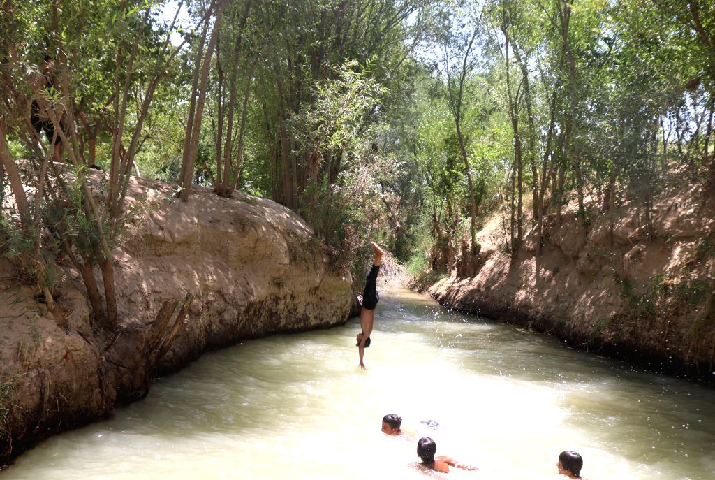 JAWZJAN, July 20, 2019 - Children cool themselves in a canal during a hot day in Shiberghan, capital of northern Jawzjan province, Afghanistan, July 19, 2019.