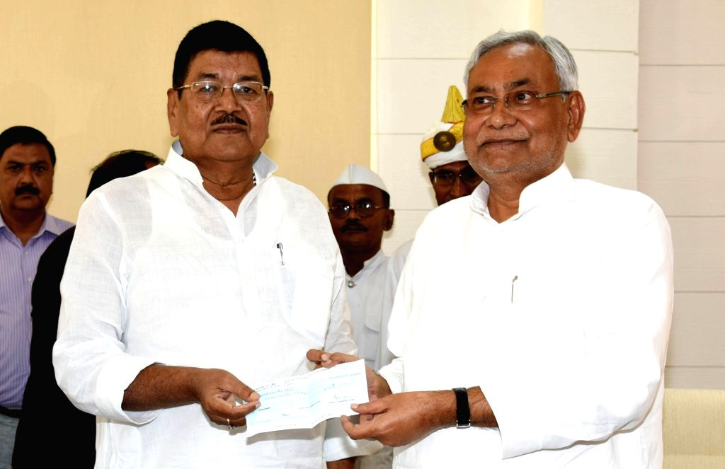 JD(U) MP Dinesh Chandra Yadav presents a cheque to Bihar Chief Minister Nitish Kumar as a contribution to the Chief Minister's Relief Fund in Patna on Sept 11, 2017. - Nitish Kumar and Dinesh Chandra Yadav