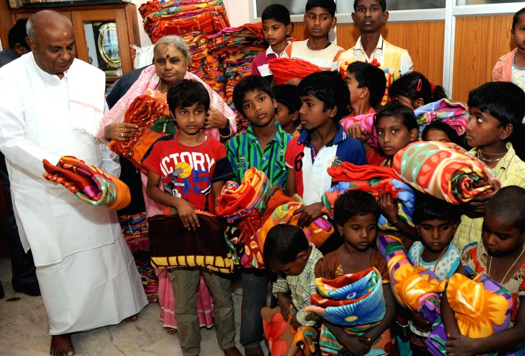 JDS National President H D Devegowda with wife Chennamma Deve Gowda distribute 2000 blanket for the homeless children at their residence in Bengaluru, on Jan 16, 2016.