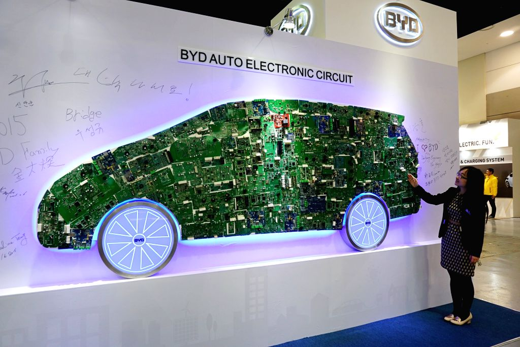 A staff of BYD Auto Co. introduces the electronic circuit of a BYD car during the International Electric Vehicle Expo (IEVE) held in Jeju island of South Korea, on ...