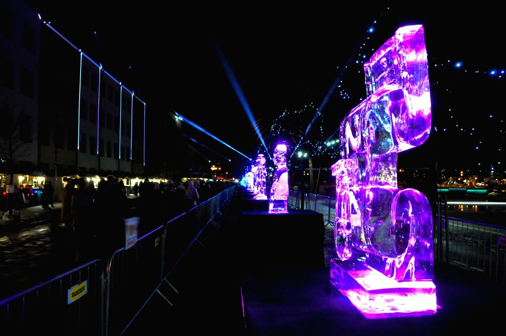 JELGAVA, Feb. 9, 2019 - People look at the ice sculptures during the International Ice Sculpture Festival in Jelgava, Latvia, Feb. 8, 2019. More than 65 ice sculptures and various ice objects are ...