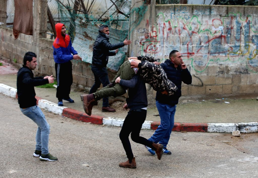 JENIN, Jan. 18, 2018 - Palestinians evacuate a wounded protester during clashes with Israeli forces in the West Bank city of Jenin, on Jan. 18, 2018. Palestinian sources said Thursday a Palestinian ...