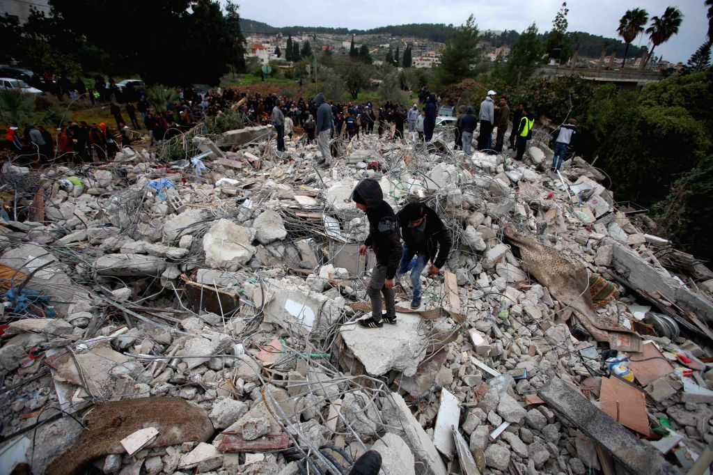JENIN, Jan. 18, 2018 - Palestinians inspect the damage of the house demolished by Israeli forces during a military operation in the West Bank city of Jenin, on Jan. 18, 2018. The Israeli forces ...