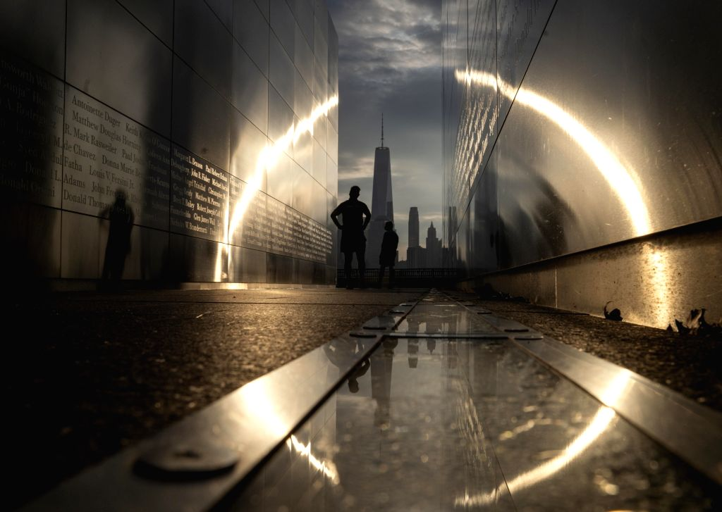 Jersey City (U.S.), Sept. 11, 2020 People are silhouetted against sunrise inside the Empty Sky memorial at Liberty State Park in Jersey City of New Jersey, the United States, on Sept. 11, ...