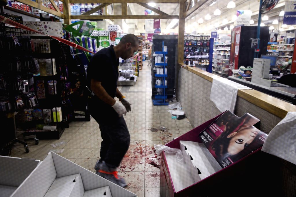 An Israeli security member inspects the scene where an attack occurred at Rami Levi supermarket in the industrial zone of Mishor Adumim, east of Jerusalem, on Dec. 3, 2014. A Palestinian ..