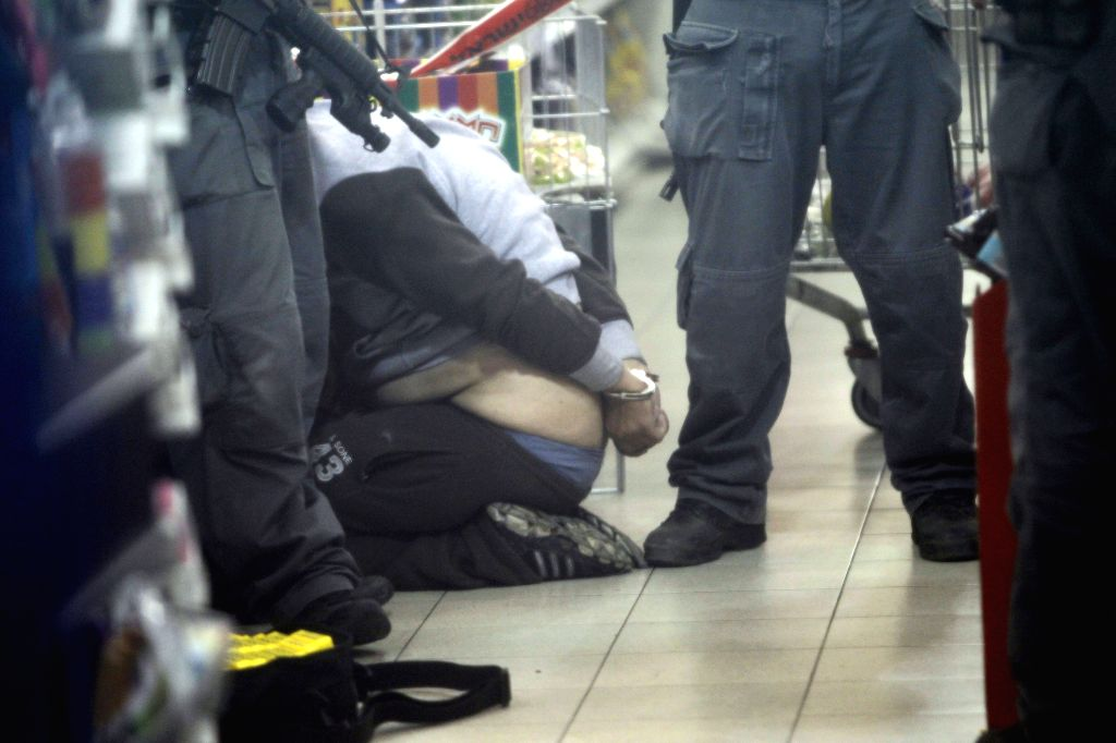 An suspect is captured by Israeli security members on the scene where an attack occurred at Rami Levi supermarket in the industrial zone of Mishor Adumim, east of Jerusalem, on Dec. 3, ...