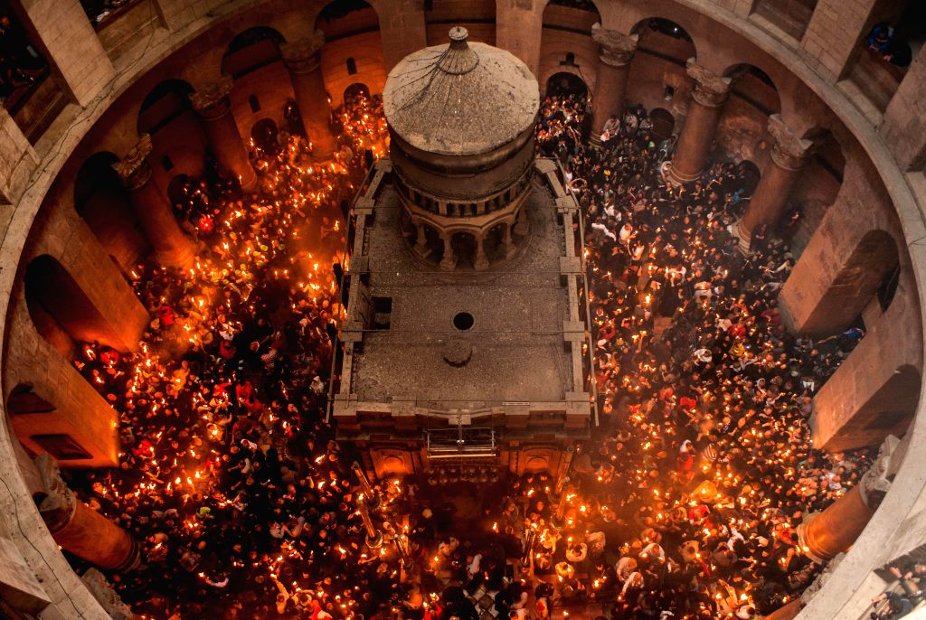 Worshippers hold candles as they take part in the Orthodox Christian Holy Fire ceremony at the Church of the Holy Sepulchre in the Old City of Jerusalem, on ...